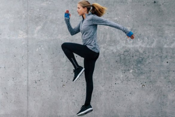 Woman raising knee and warming up for sport